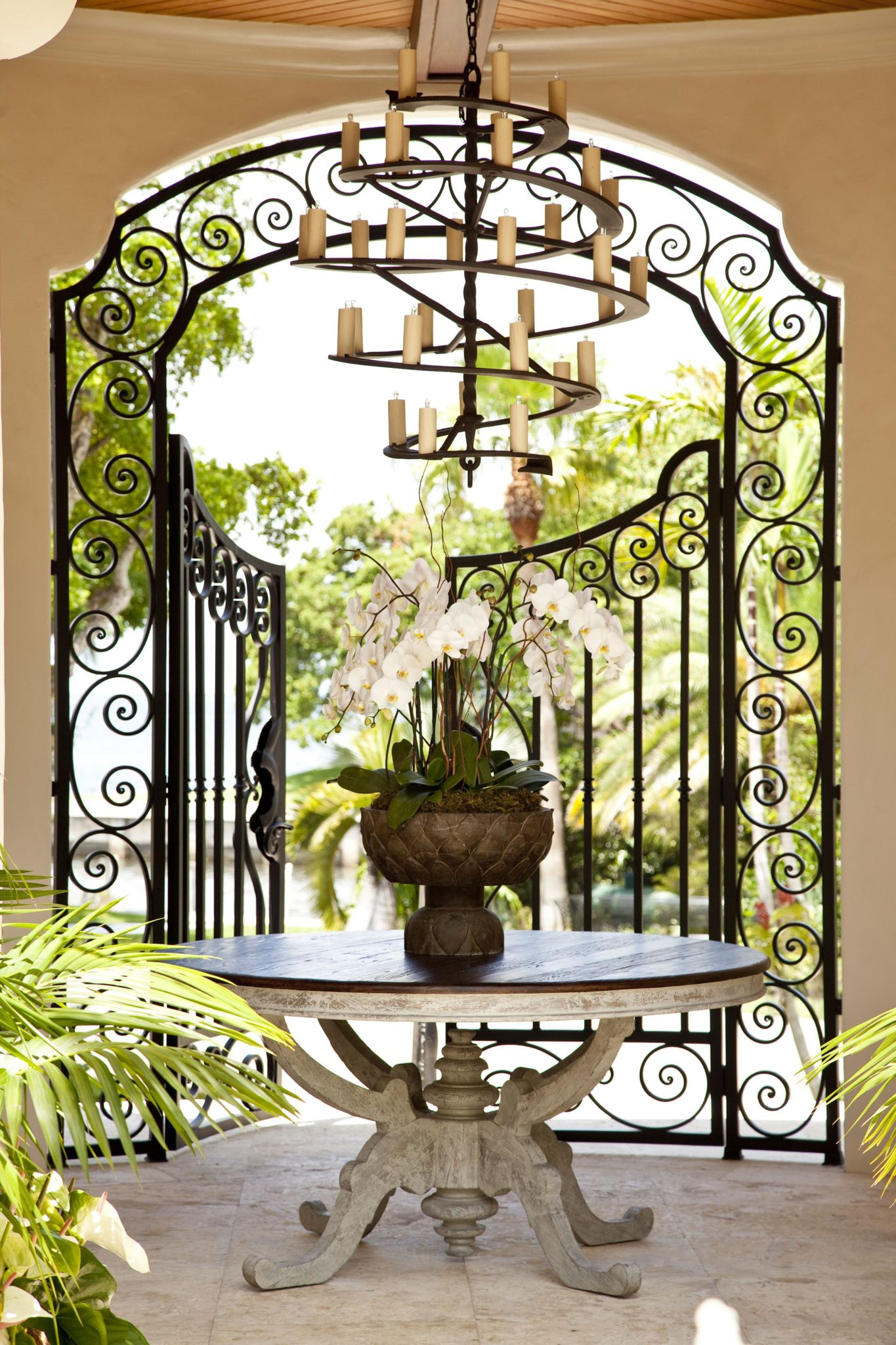 Wrought iron details including a entry gate and a candlelit chandelier. by Taylor & Taylor