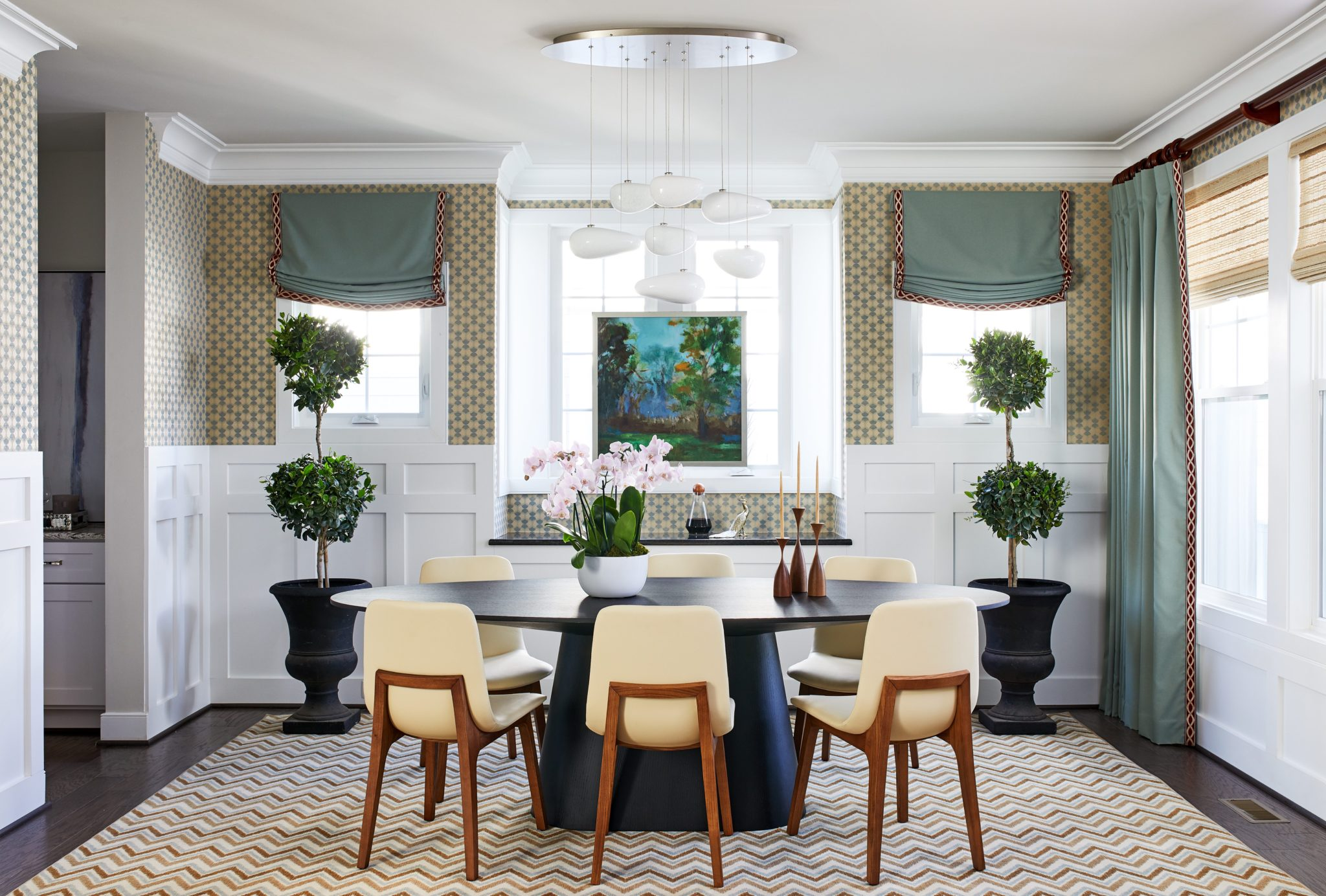 Wainscoting, grasscloth chandelier geometric zig zag rug walls blue drapes shade by Dane Austin Design