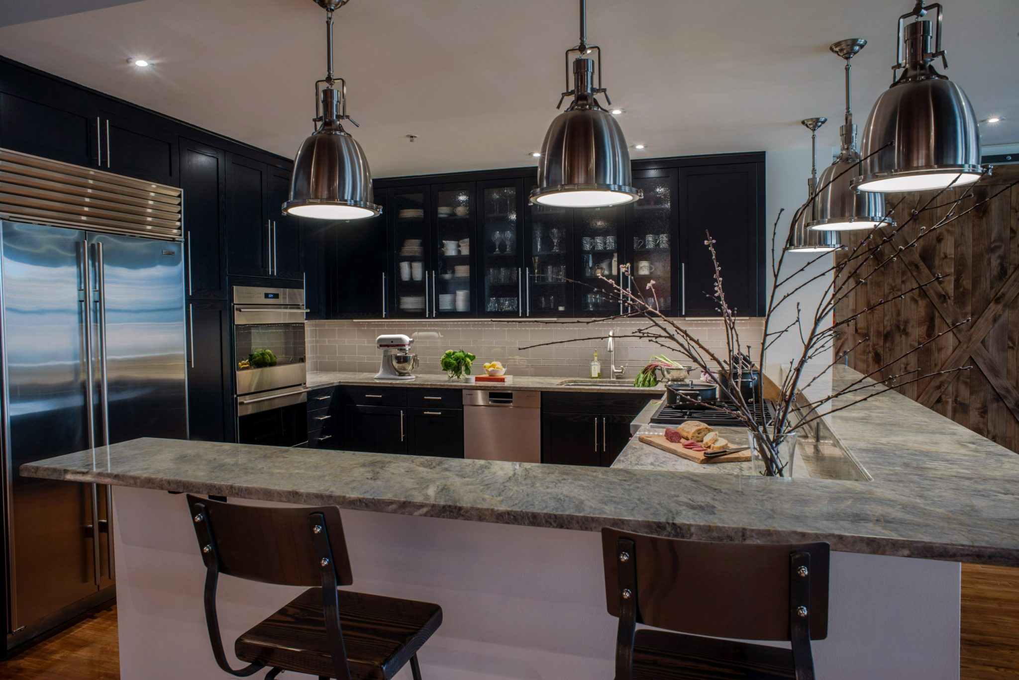 Contemporary Kitchen with Black Cabinetry and Industrial Touches by Michele Plachter Design