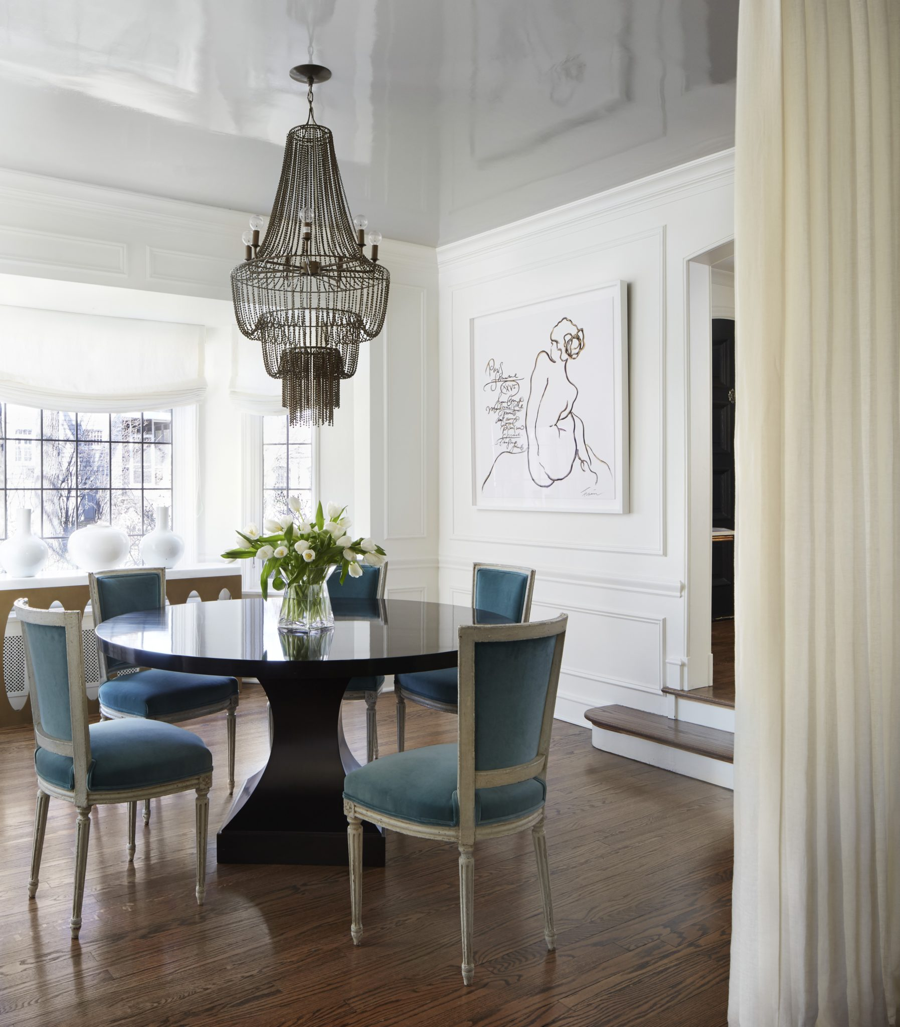 A dining room with lacquer ceiling, chandelier and custom art by Amy Kartheiser Design