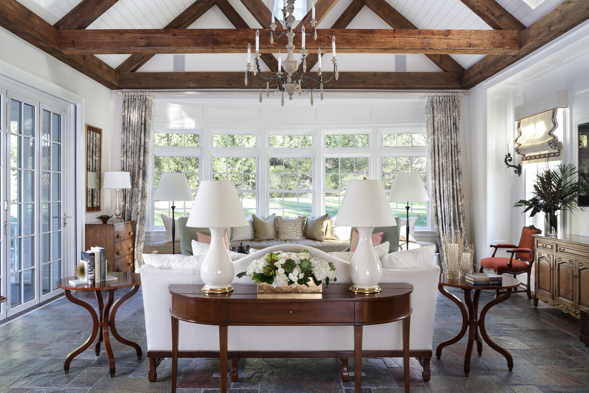 Sunroom featuring claved slate floor, reclaimed beams, window seat, nano door to dining area by J. Stephens Interiors