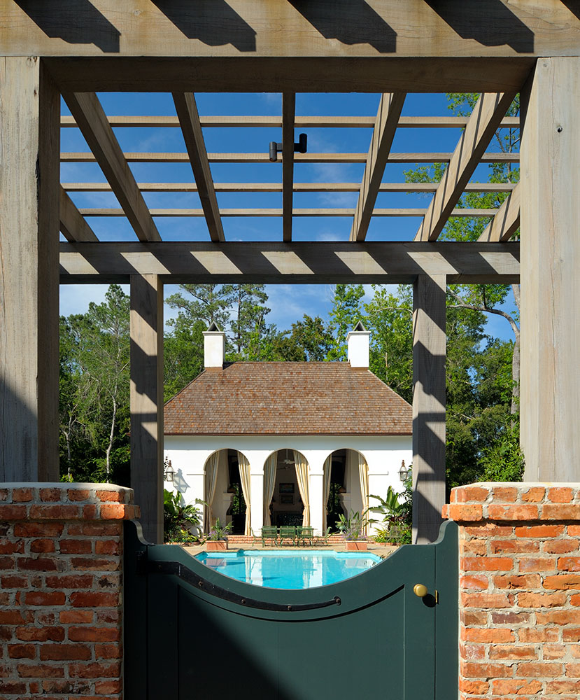 Pergola and gate frame the French Colonial Pool House. by Ken Tate Architect