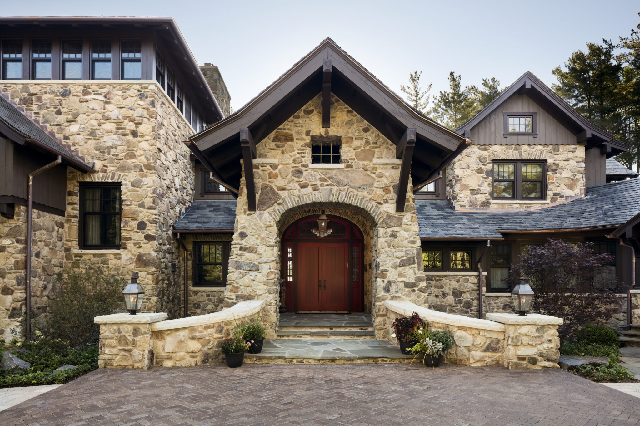 Bright red doors add a pop of color to the neutral stone exterior. By Wade Weissmann Architecture Inc.