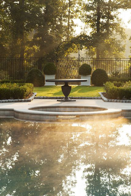 Pool and Spa detail in the mist. Indiana limestone terrace and iron fencing. by Howard Design Studio
