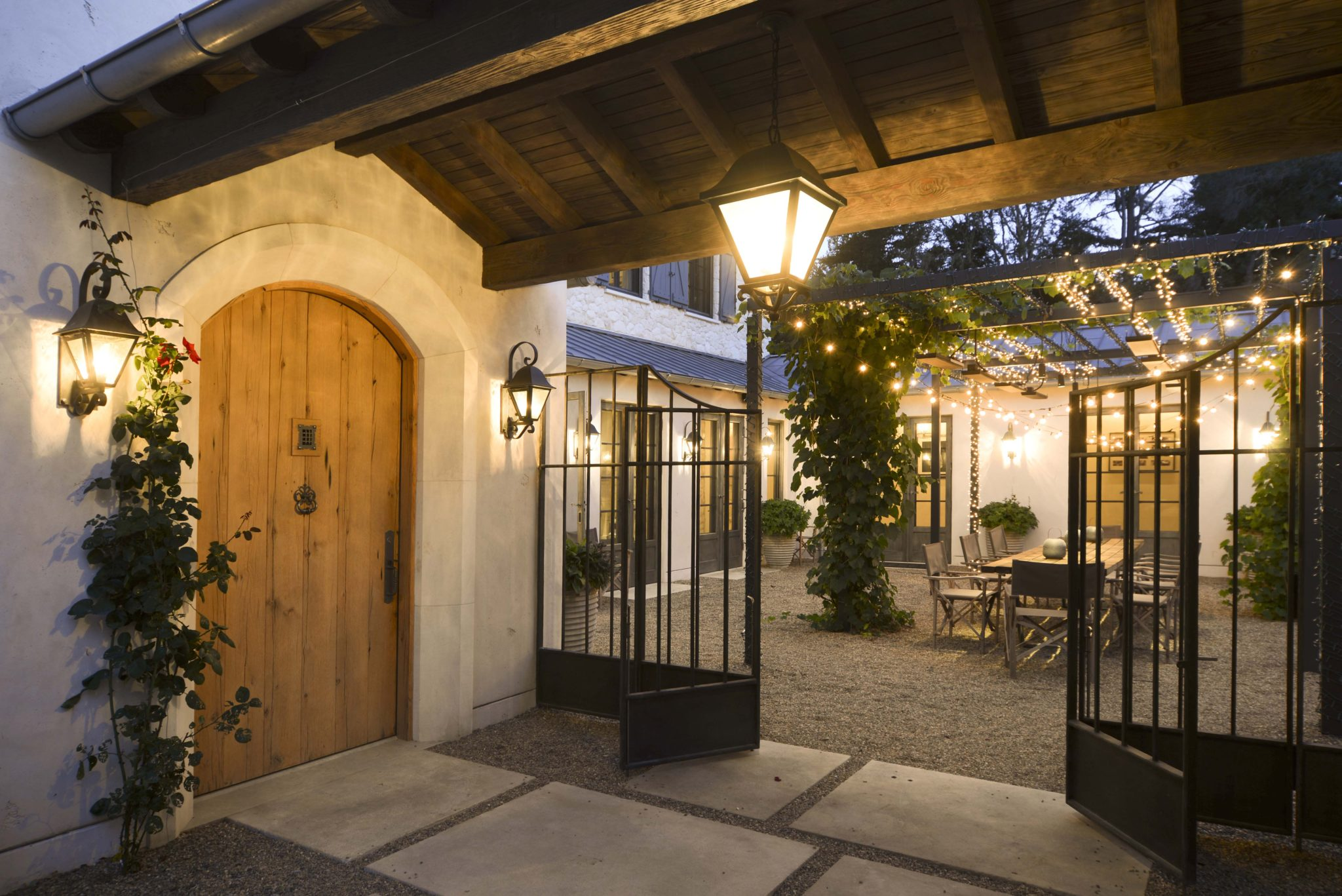 French stone residence entryway, dining courtyard with lights and vine trellis by Fergus Garber Young Architects