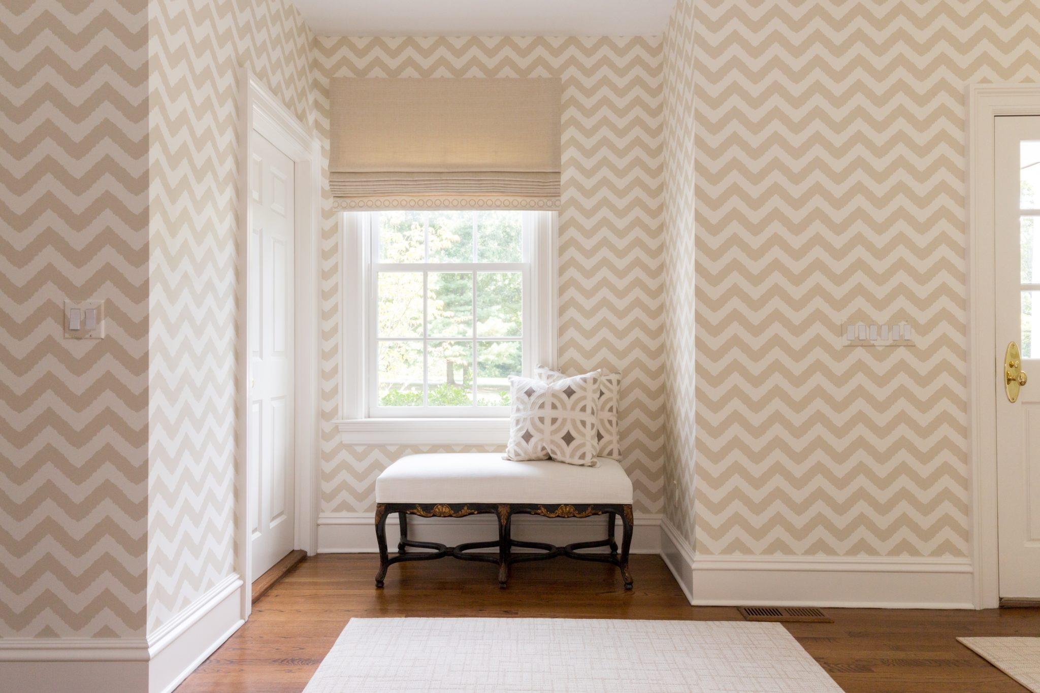 Neutral chevron wallpaper in this hallway juxtaposes the dark wood floors. by Reed & Acanthus Interior Design