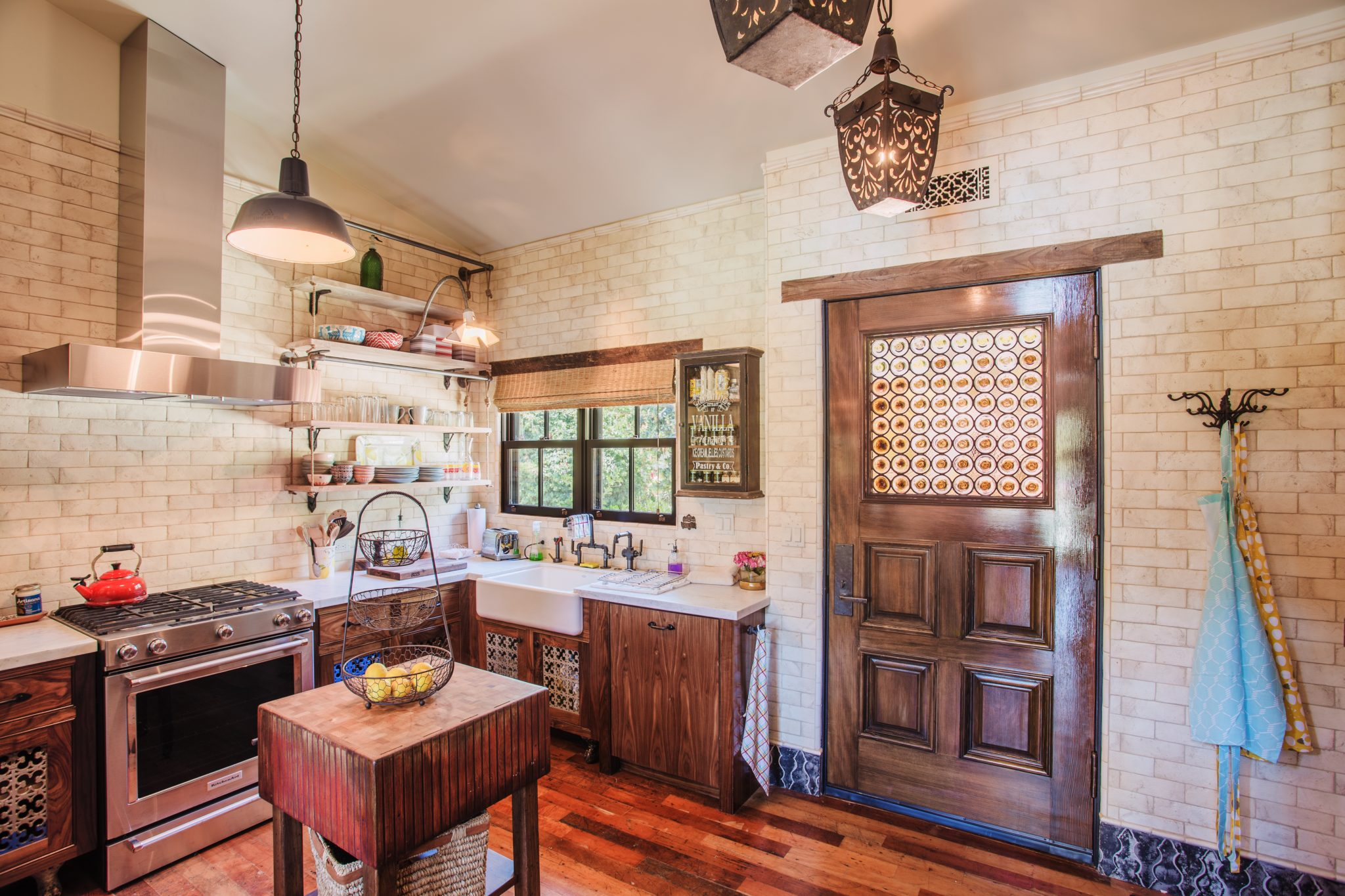 A rustic kitchen with neutral brick walls, hardwood floors and lantern lights. by Wade Weissmann Architecture Inc.