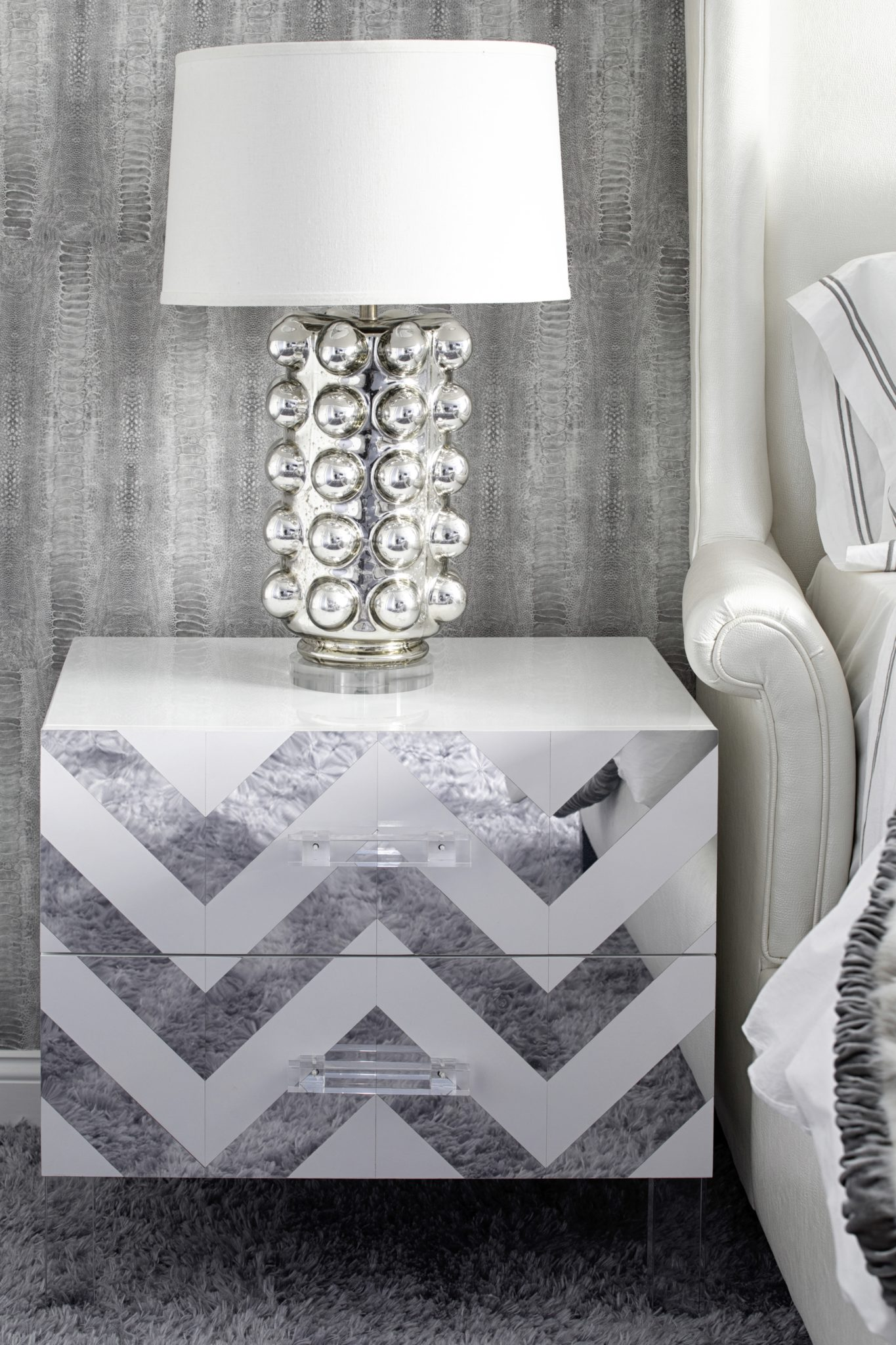 Metallics shine with a chevron mirror side table, mercury glass lamp & wallpaper by Laura Michaels Design