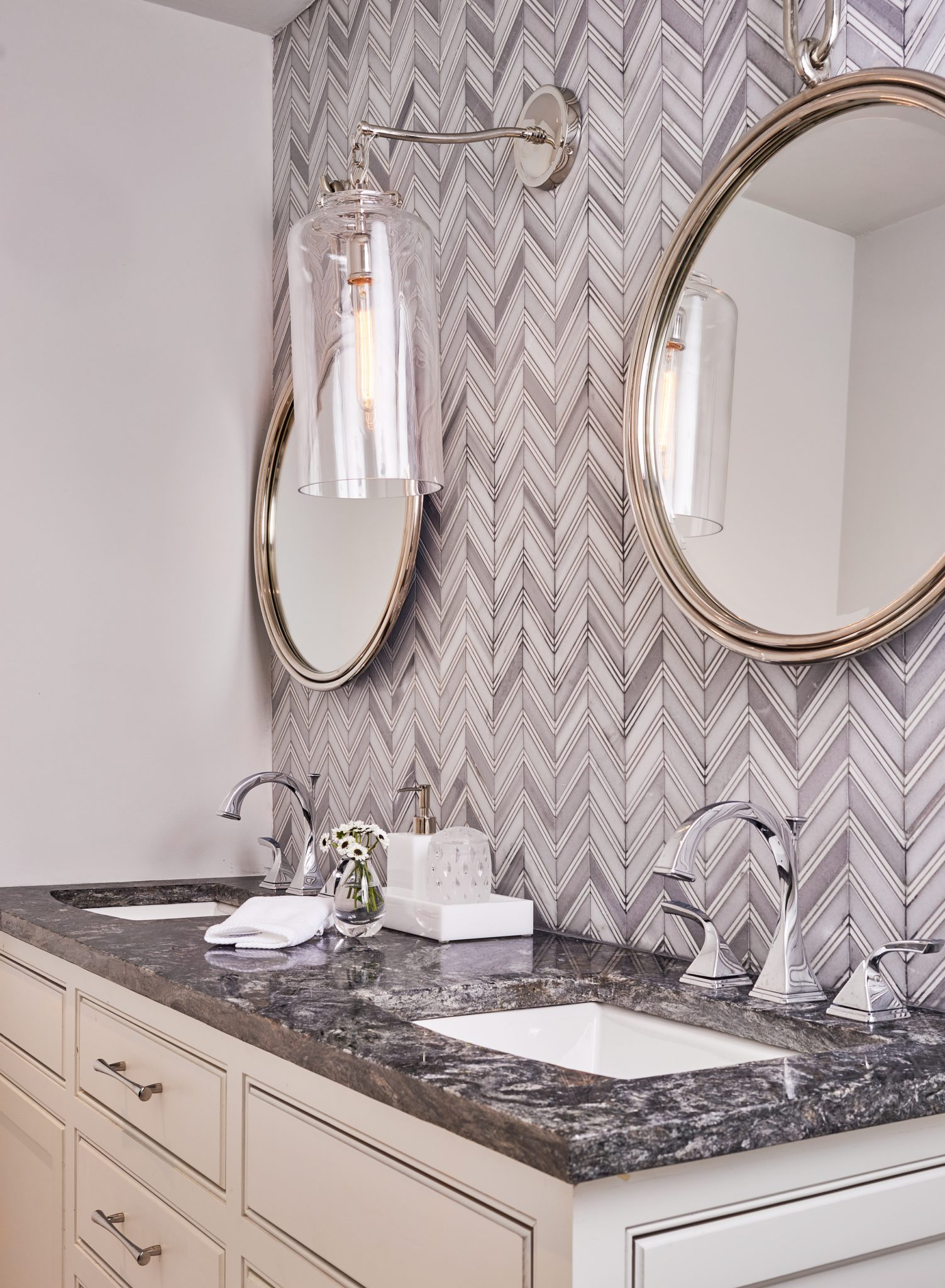 Marble chevron and polished nickel provide a sparkling, clean look to the space. by Wesley-Wayne Interiors