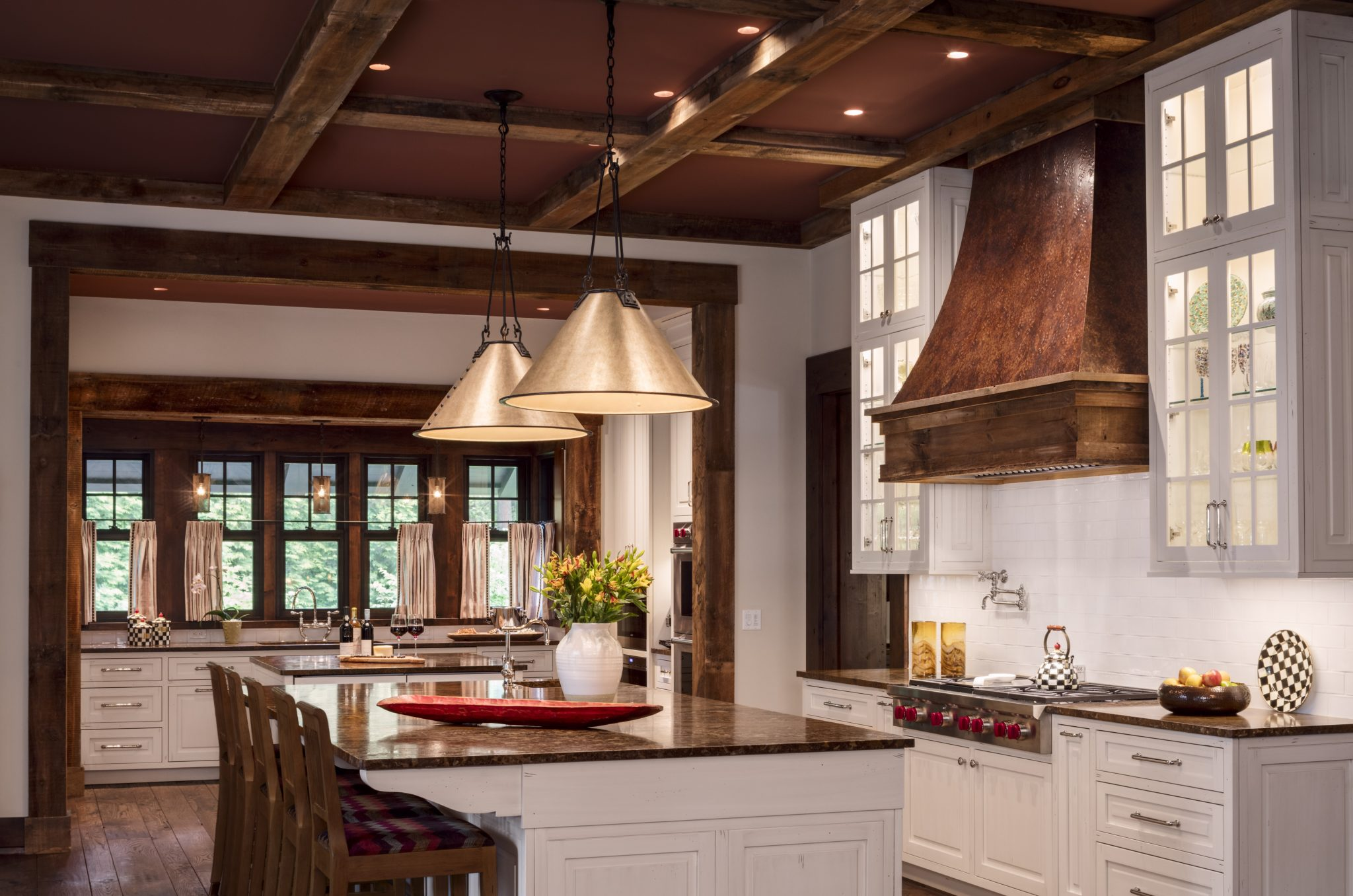 Rustic kitchen features industrial lighting, wood trim and a large island by Wade Weissmann Architecture Inc.