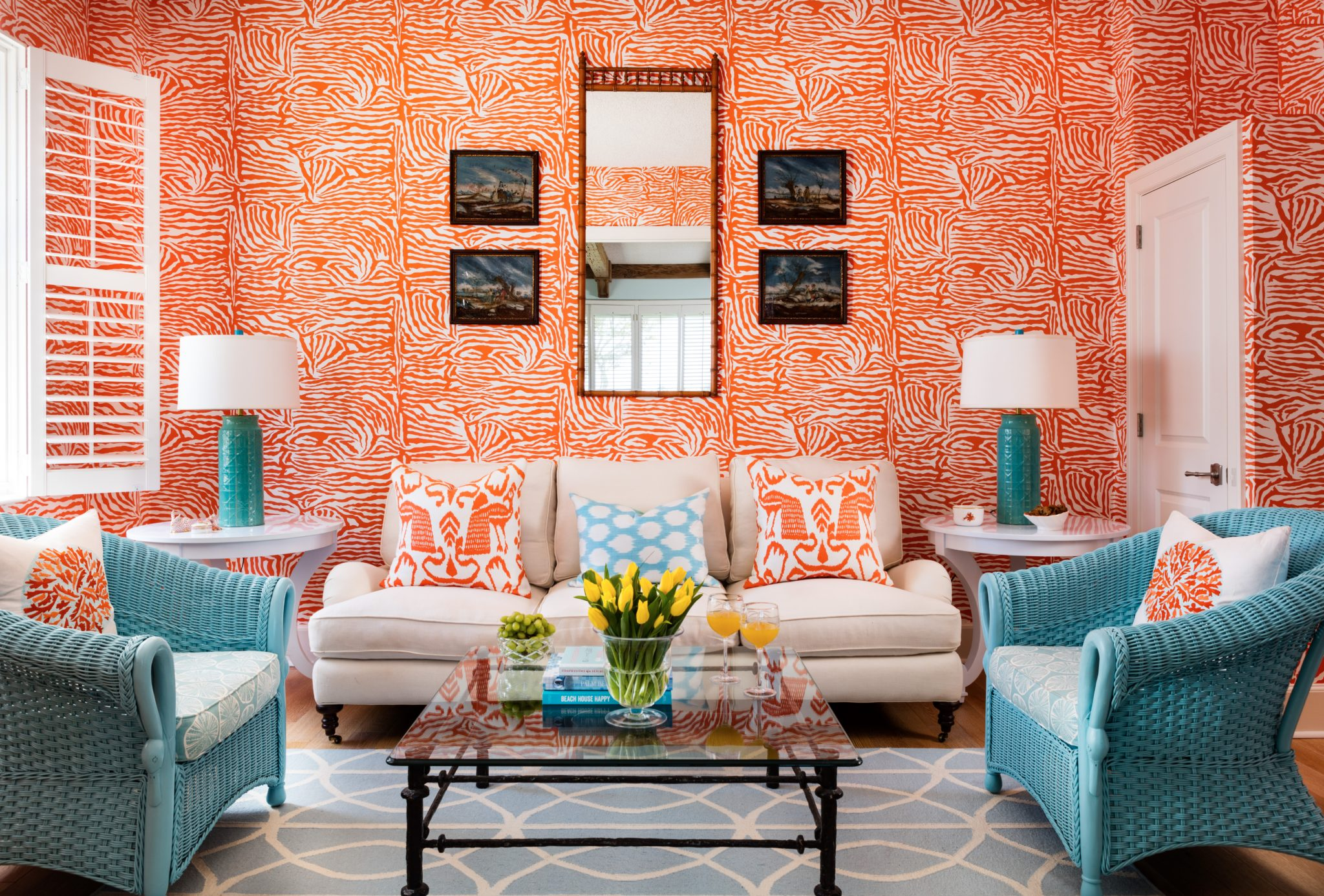 Abstract orange wallpaper is complemented by light blue wicker chairs. By Gil Walsh Interiors