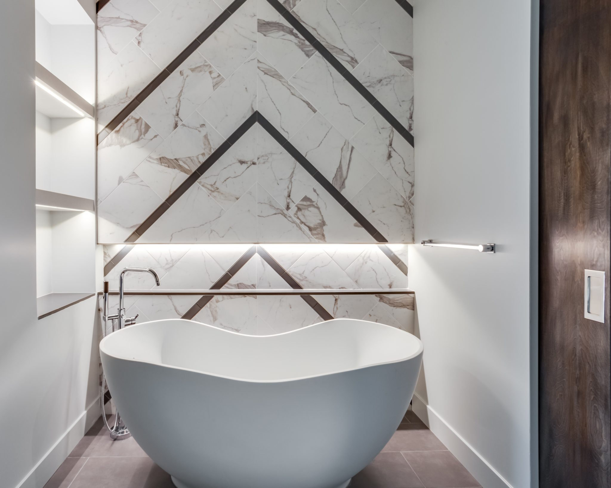 Freestanding tub in master bathroom with chevron white marble wall by Wendy Glaister Interiors
