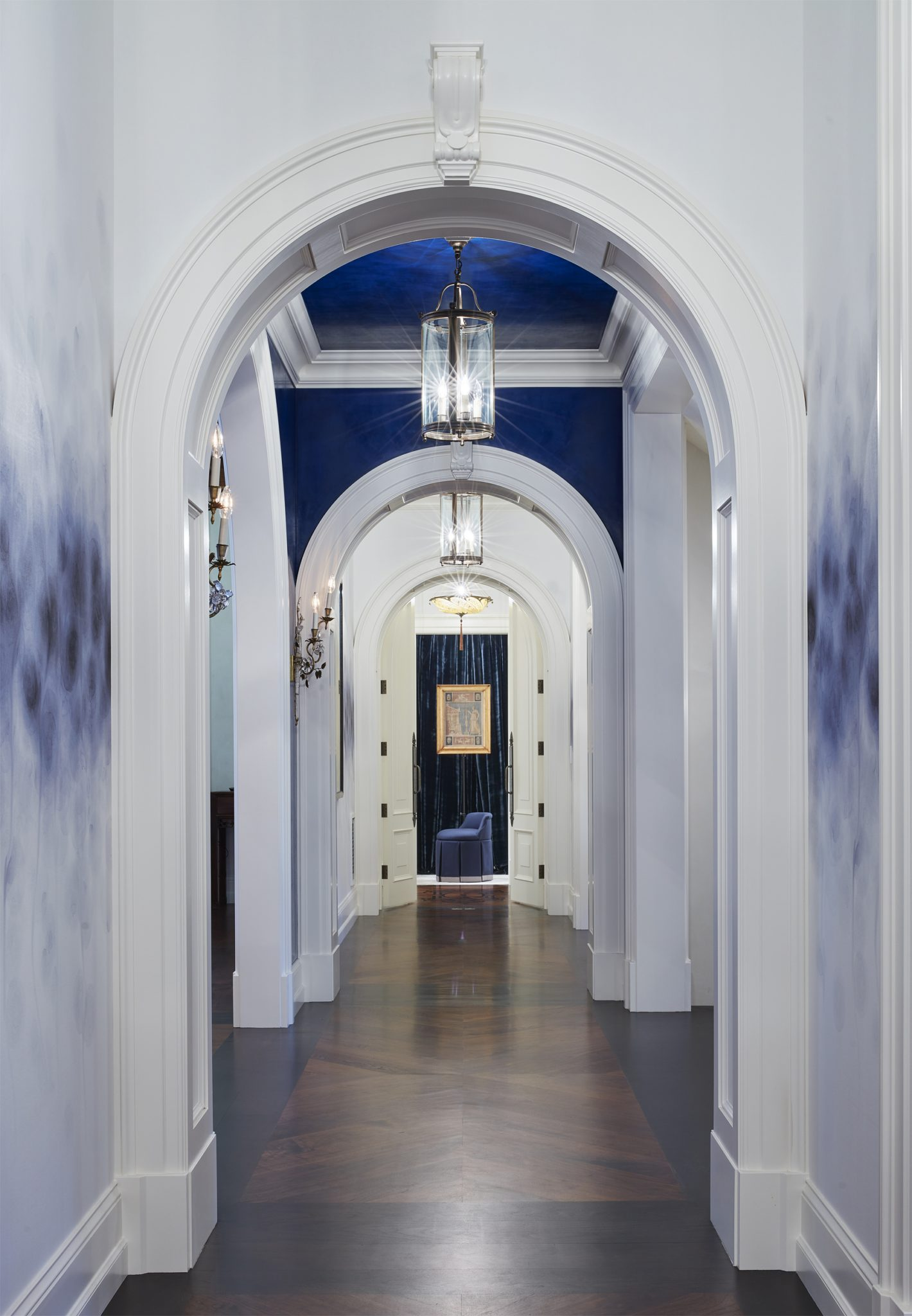 Series of paneled archways hover over a chevron inlaid wood floor by Murphy & Co. Design
