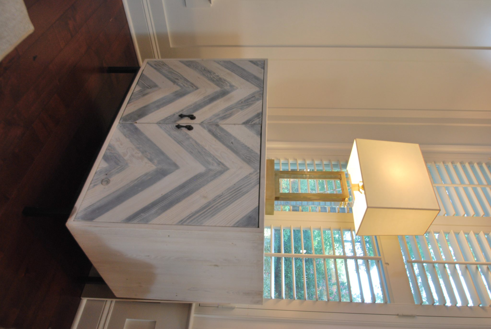 Virginia modern farmhouse family room gray and white chevron cabinet and lamp. by Michael Molesky Interior Design