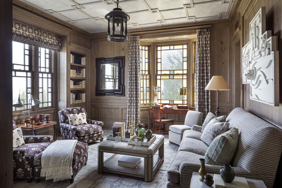 In the library, antiqued oak walls are paired with a plaster ceiling overlaid with a Chinoiserie fretwork. A wall sculpture by Louise Nevelson relates to the geometry and color of the ceiling.