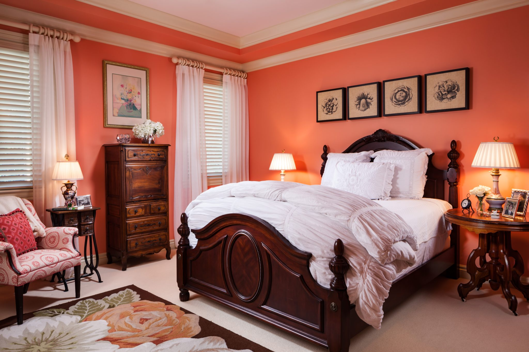 A beautiful contrast of pastel peach walls with carved solid walnut bedroom furniture fills this bedroom with warmth. By Gil Walsh Interiors
