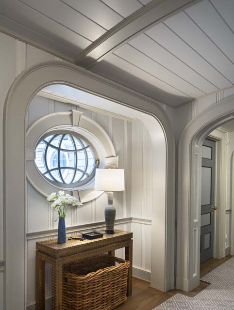 An operable elliptical window in a second-floor stair hall alcove.