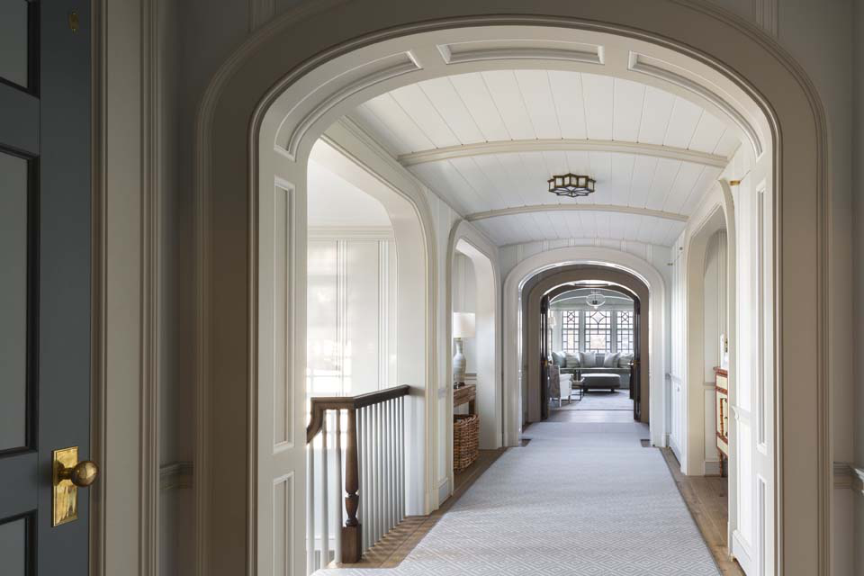 The second-floor stair landing features a shallow vaulted ceiling and enfilade of arched cased openings.