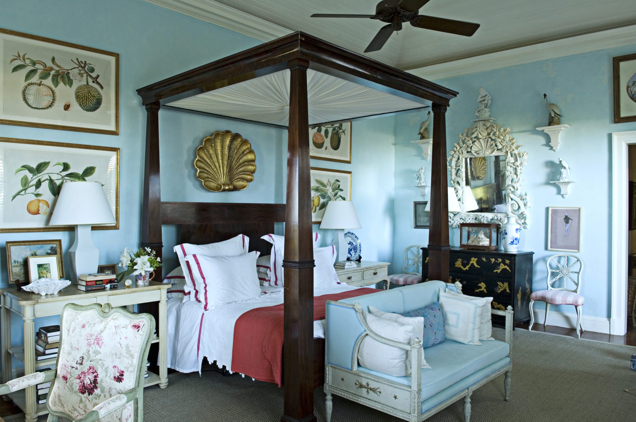 A vivid turquoise Venetian plaster is used on the walls of this tropical bedroom by Bunny Williams Inc.