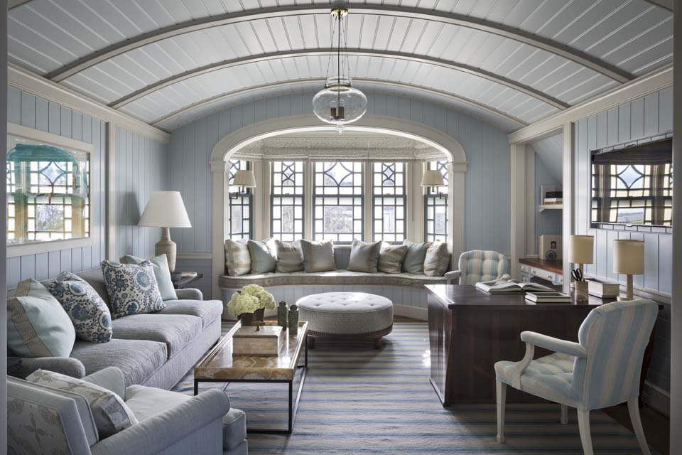 The master sitting room, at the end of the second-floor hall, continues the vault-and-beam motif. Above the window seat a diamond-patterned window combines milk glass and transparent panes.