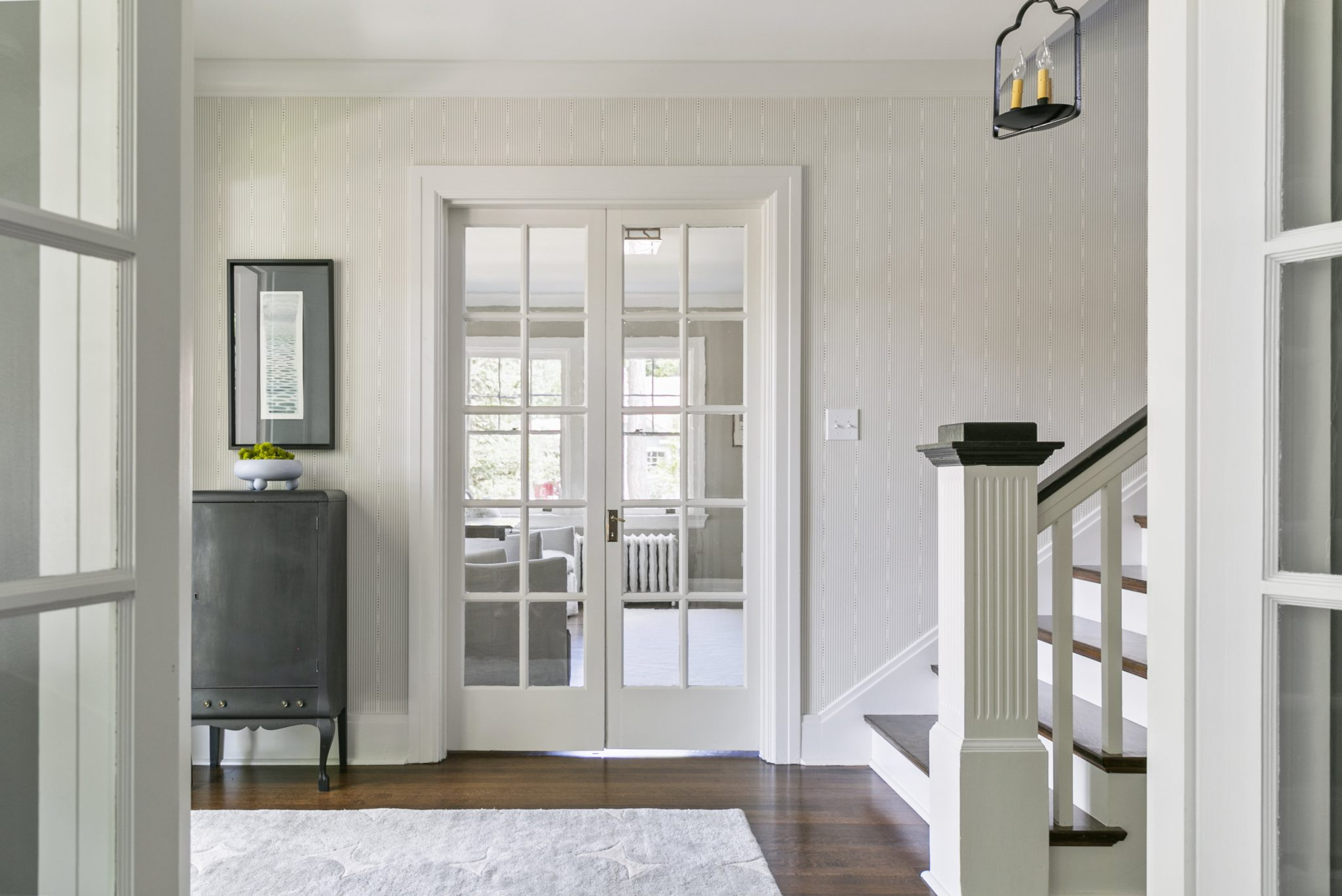 North End Boise entry foyer with metal candle pendant and vintage black cabinet by Maren Baker Design