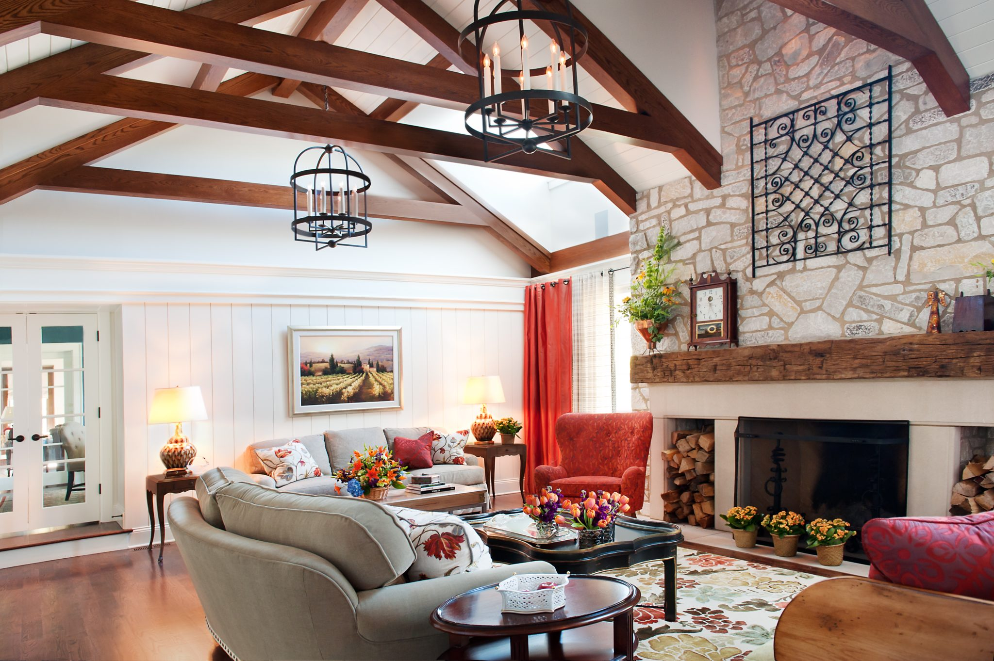 Planked ceiling + trusses with lanterns, stone fireplace, coral drapes & chair by Elizabeth Drake