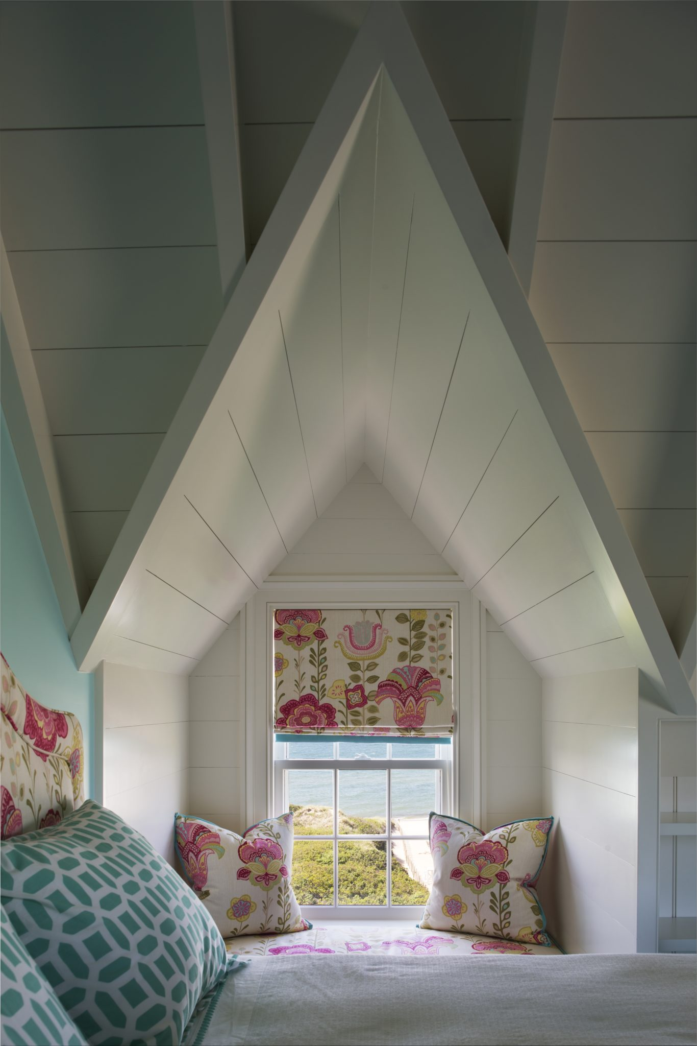 Window seat with pink floral prints, turquoise accents under a vaulted ceiling by SLC Interiors