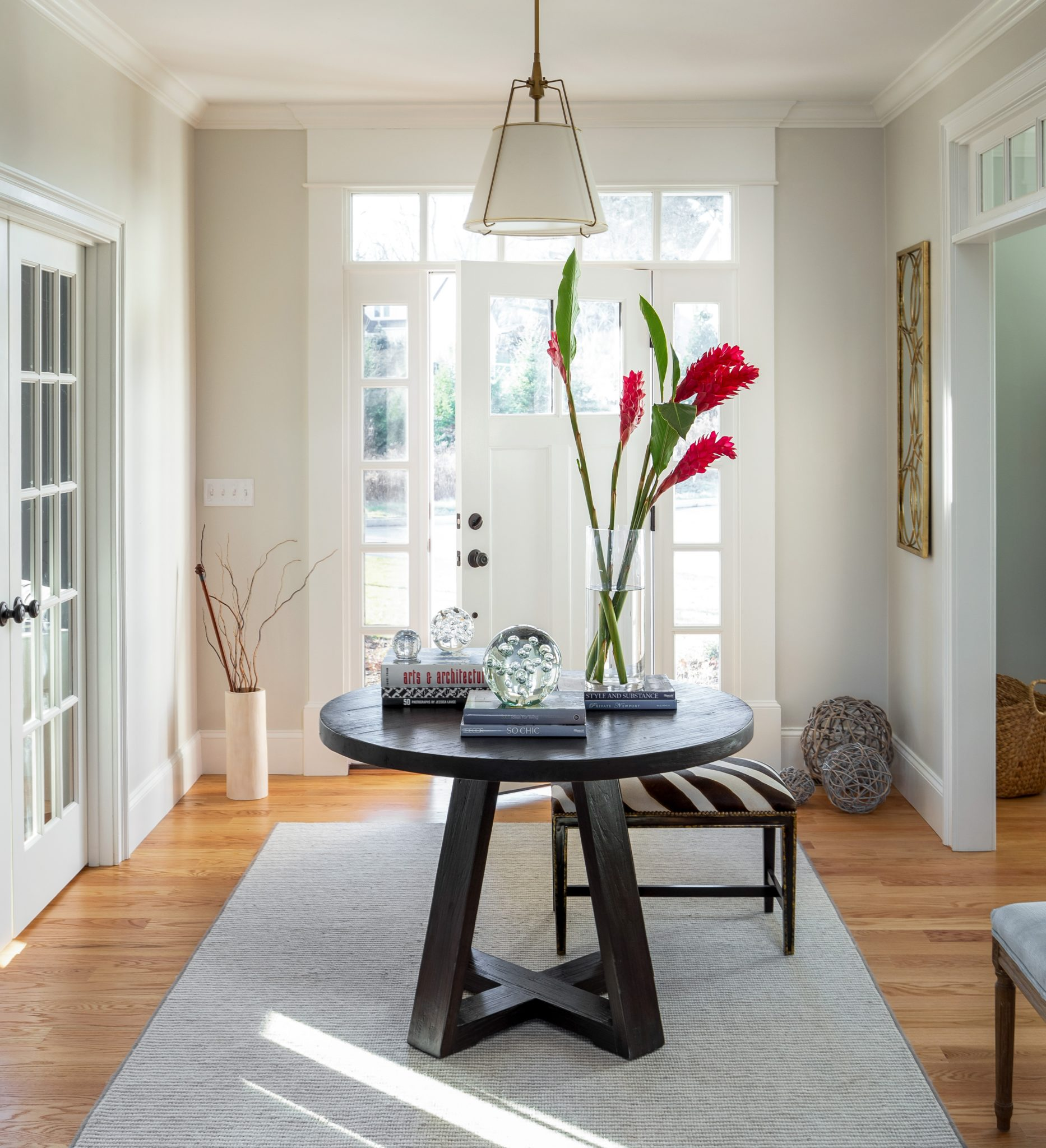 Modern neutral foyer w center table, shade pendant, zebra bench by Sophia Shibles Interiors (formerly SCS Design)