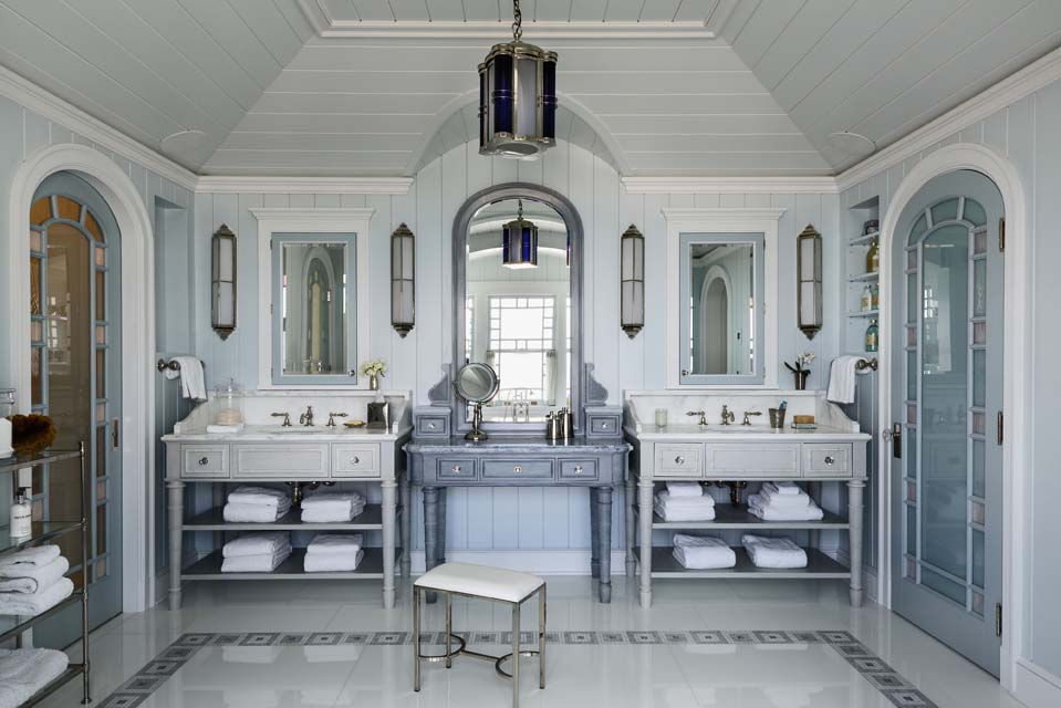 """In the master bathroom, a dressing table stands between twin vanities. The pattern in the floor and doors brings in the """"woven"""" motif found throughout the interior and exterior details of the house."""
