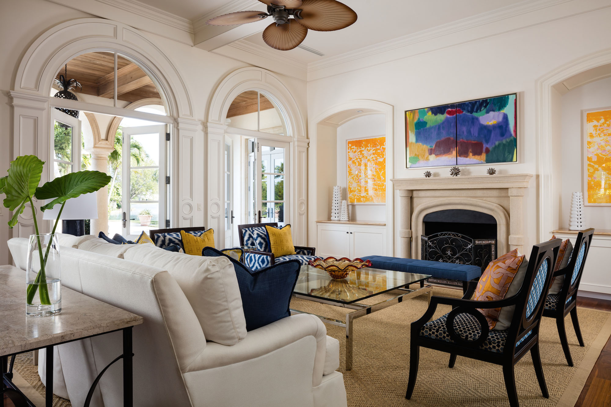 Designer Gil Walsh used a bright white backdrop and a natural rug to let bold artwork and colorful textiles shine in this airy home in North Palm Beach.