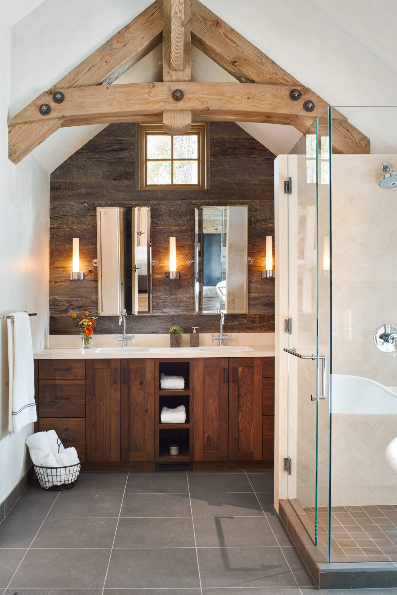 Mountain modern bath with light wood ceiling beams, glass shower and wood vanity. By Brewster McLeod Architects