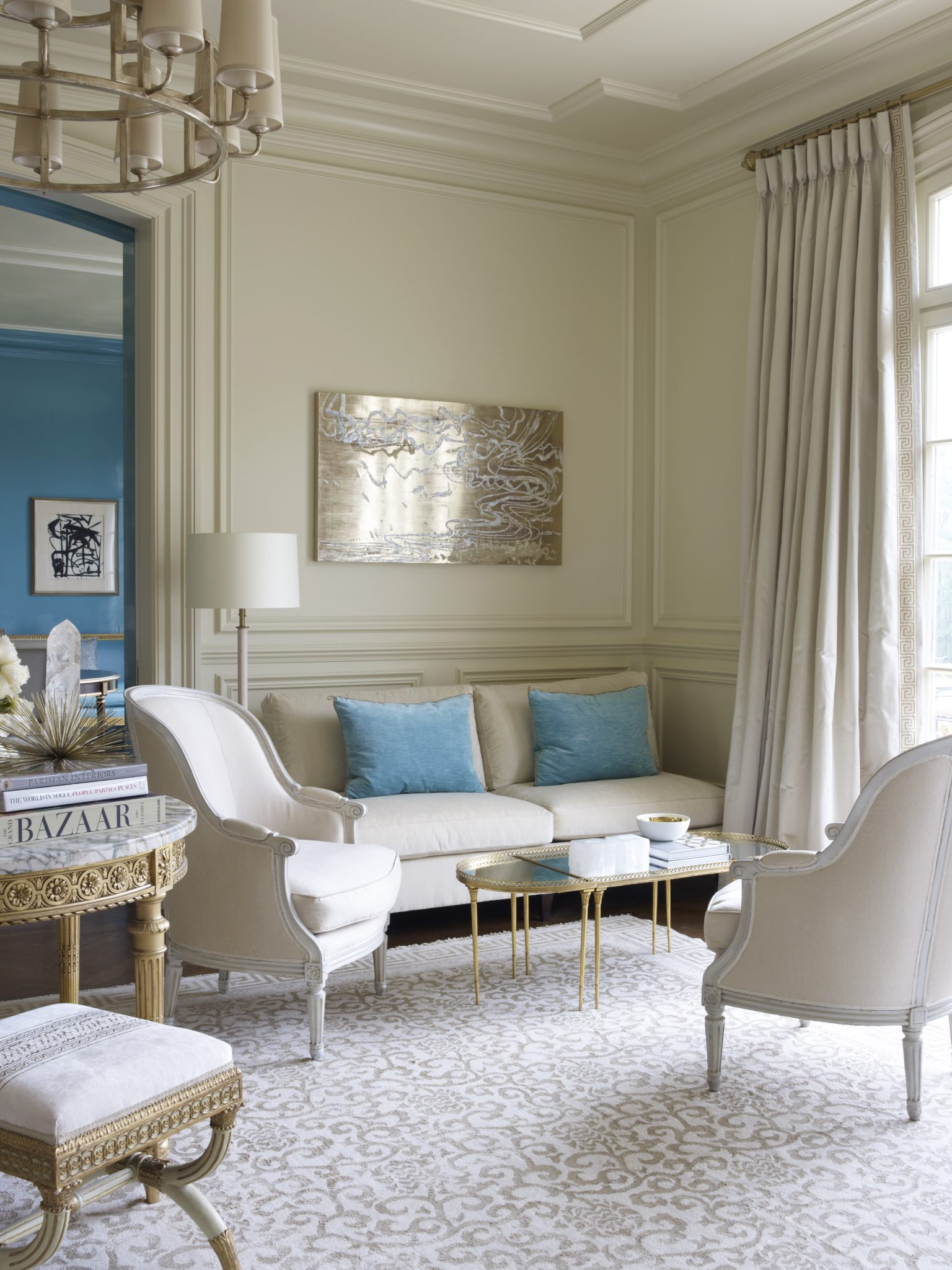 Chic neutral living room with pops of blue by Suzanne Kasler Interiors