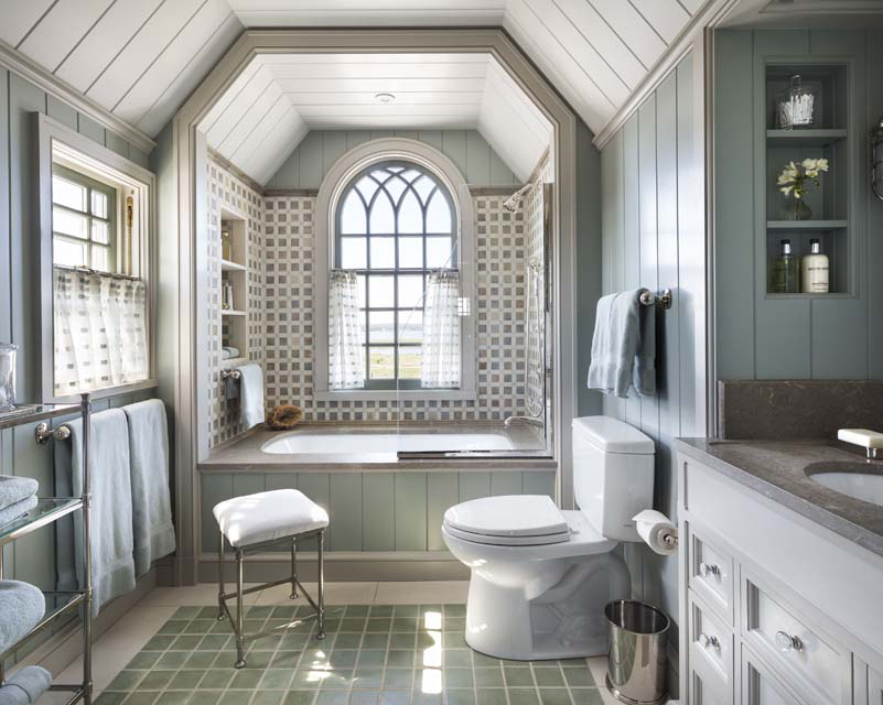 A tub alcove in one of the children's bathrooms is set into a dormer with an arched Gothic window looking toward Shinnecock Bay.