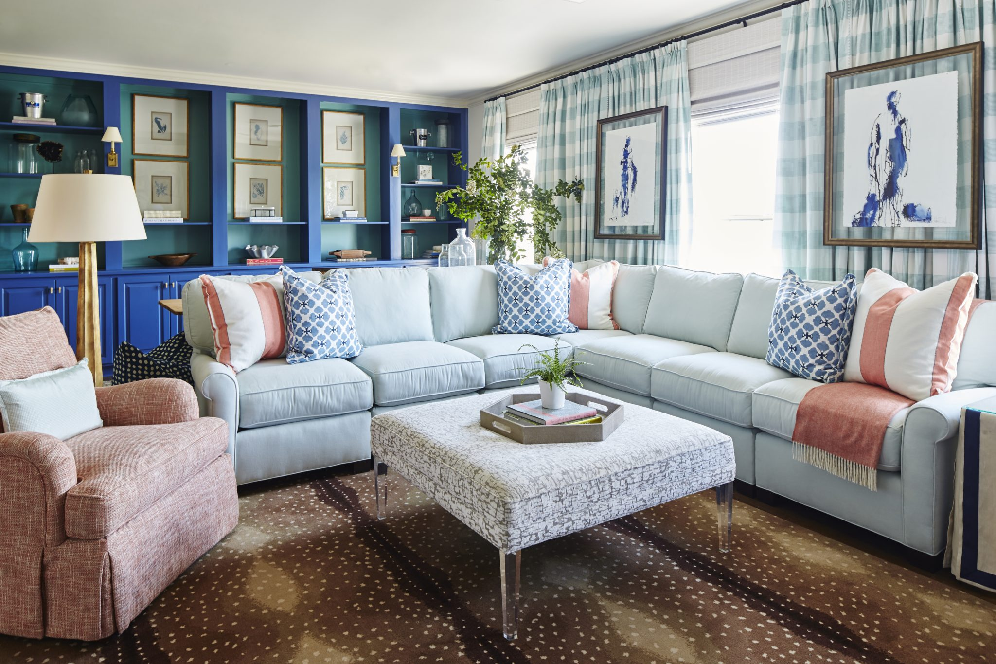 Family room with cobalt blue and turquoise cabinetry and a light blue sectional. by Ashley Gilbreath Interior Design