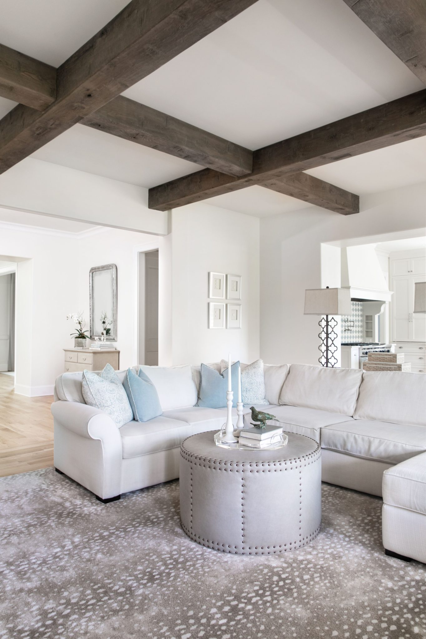 Neutral Family Room with Wooden Beams, Sectional, Drum Ottoman and Antelope Rug by Beth Brown Interiors