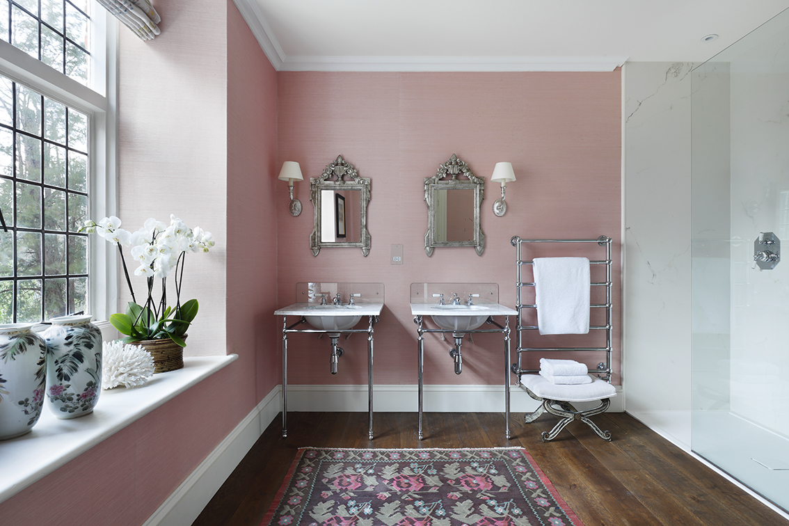 Pink wallpapered bathroom with antique mirrors and rug in country house by VSP Interiors