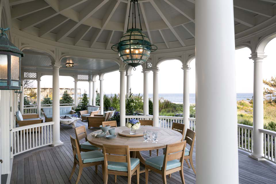 """The round dining porch is enriched with a lively pattern of exposed rafters and a """"globe"""" chandelier."""