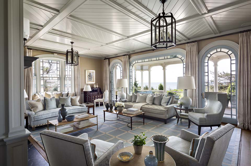 The living room seating groups arranged around the fireplace were developed by interior designer Steven Gambrel. Large windows and doors open to the panoramic ocean view.