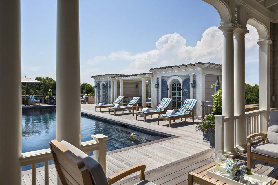 Bow-shaped rafters and a nautical-themed trellis connect the space to the dunes and pool.