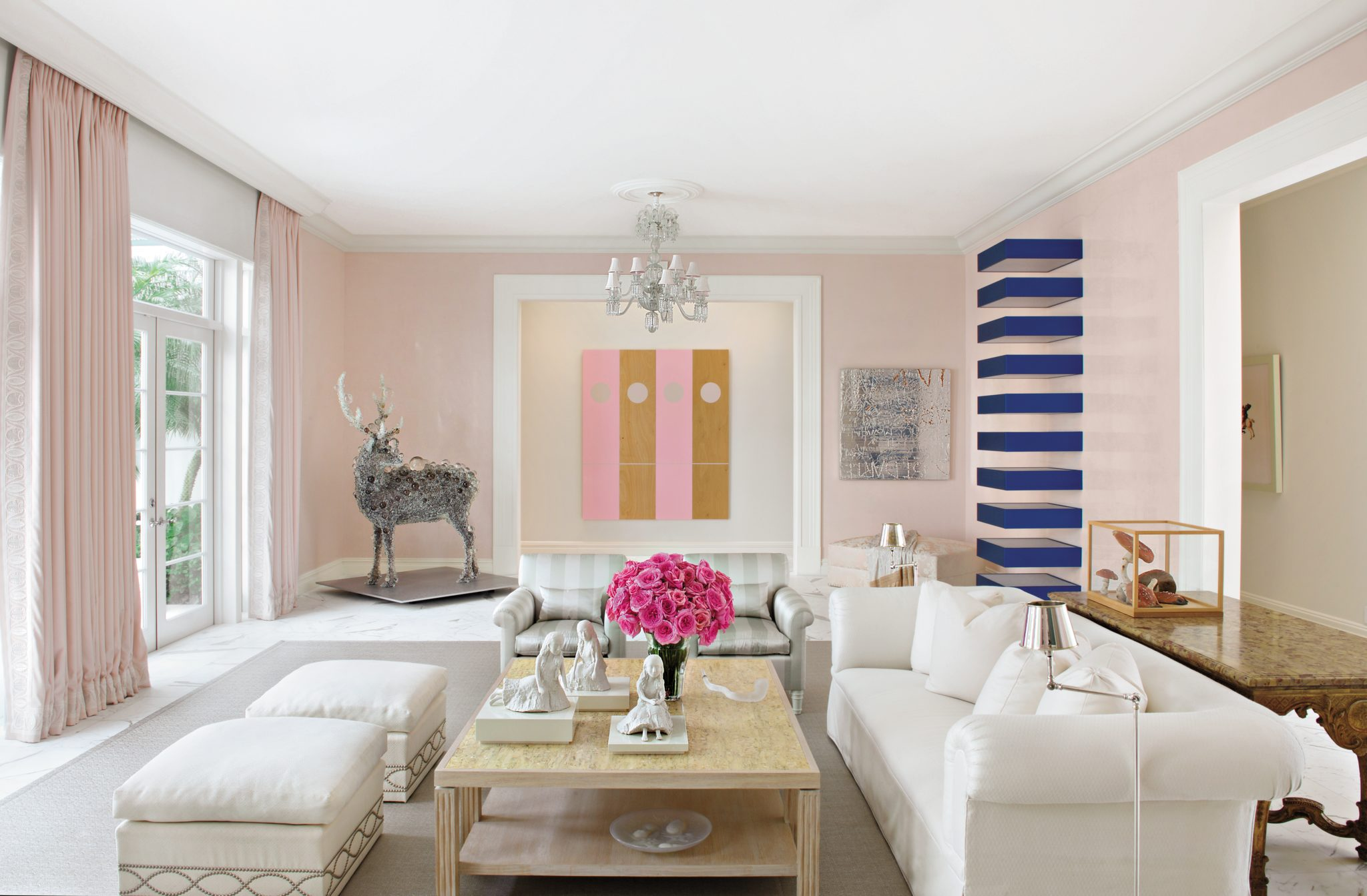 Living room in a limited palette of pale pink and white to complement the contemporary art collection by Aman & Meeks