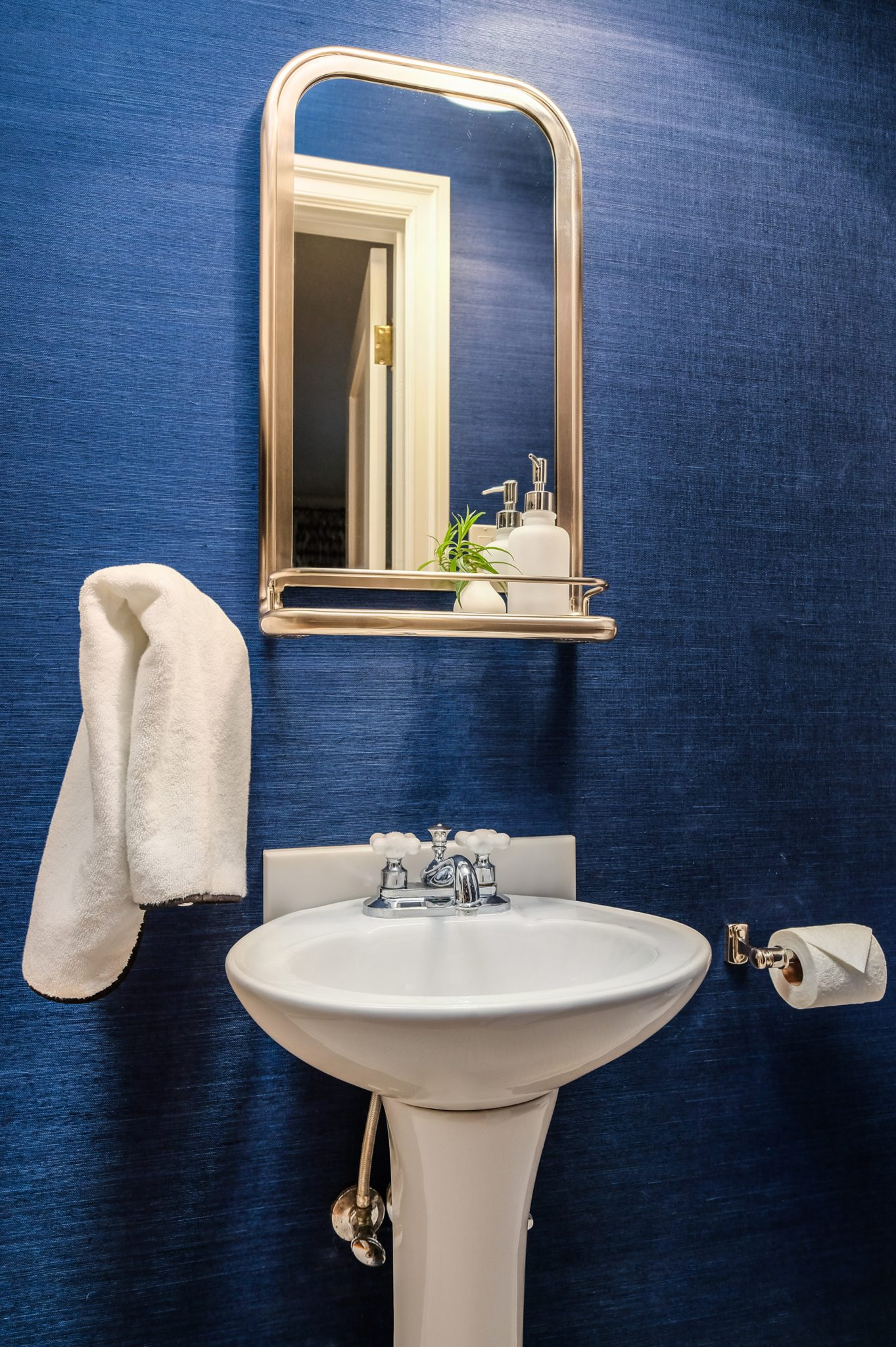 Powder room with navy grasscloth wallpaper. by MAS Design