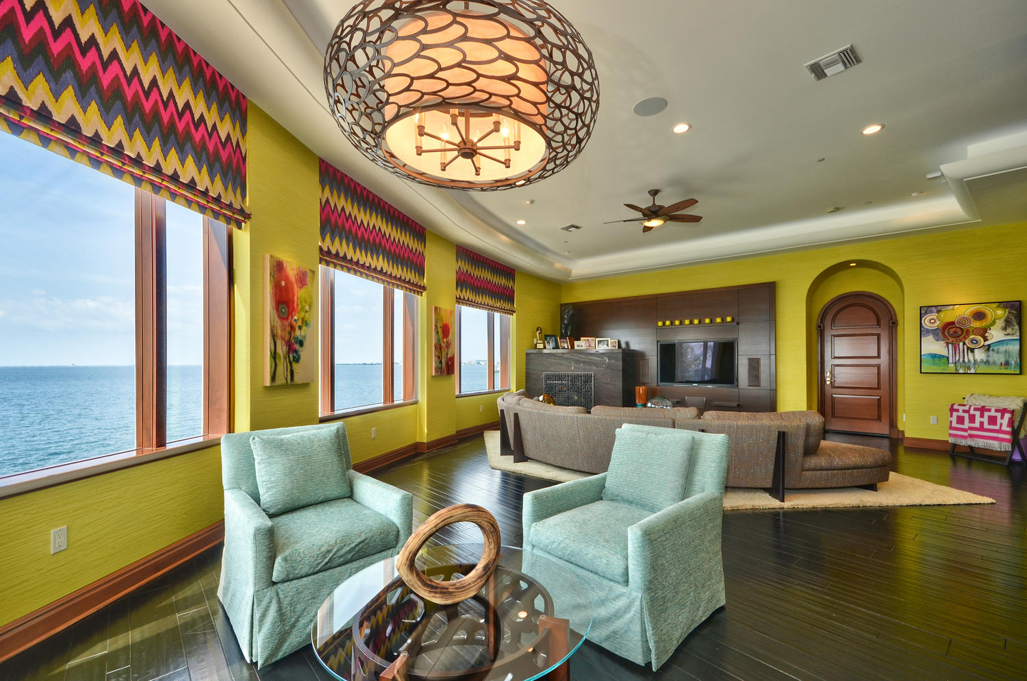 This colorful, sunny home in Tampa was designed by Crespo Design Group. The room space features a custom Italian sofa and bright roman shades in a zig zag fabric from Schumacher.
