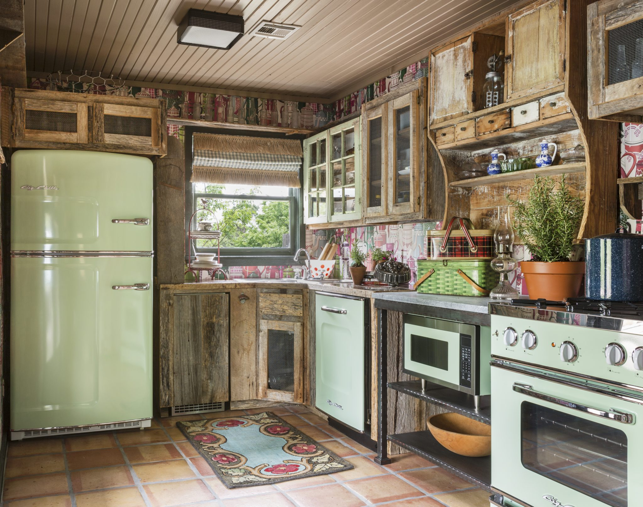 Guest cottage kitchen with mismatched cabinets and vintage-inspired appliances by Goddard Design Group