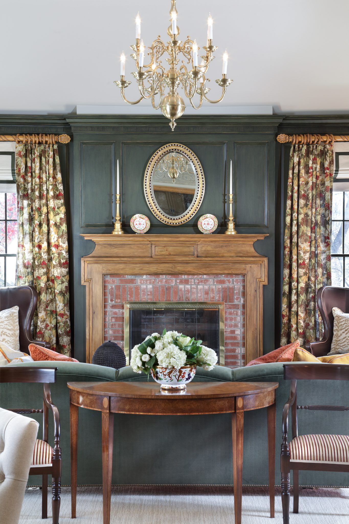 English country family room featuring green custom paneling and pine mantel by J. Stephens Interiors