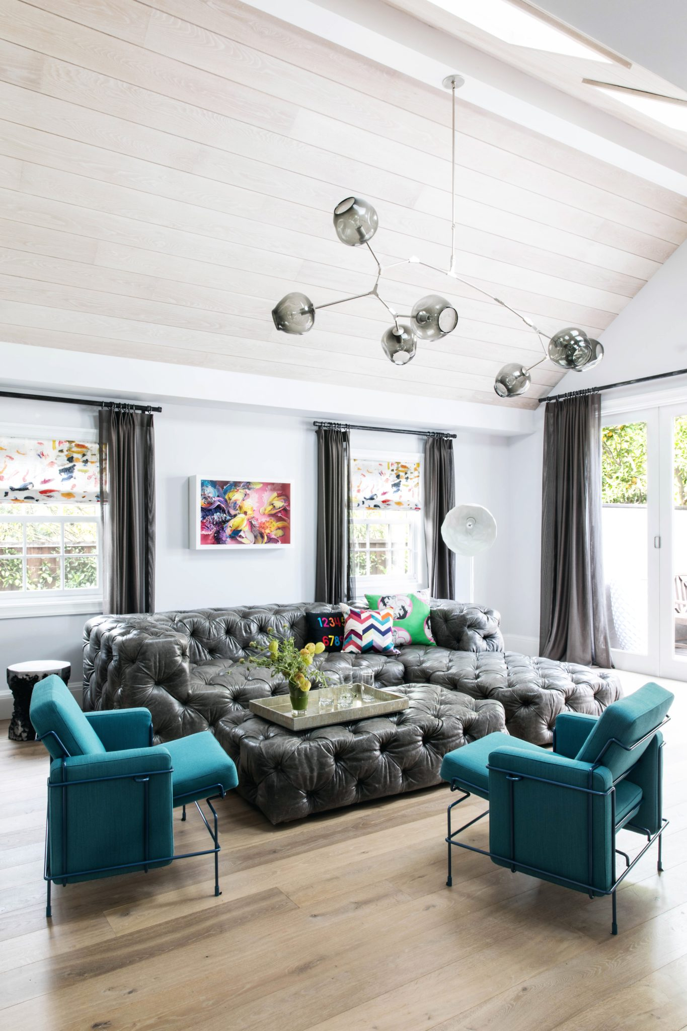 Sitting area with oversized, tufted sectional, peaked ceiling, and skylight by Jeff Schlarb Design Studio