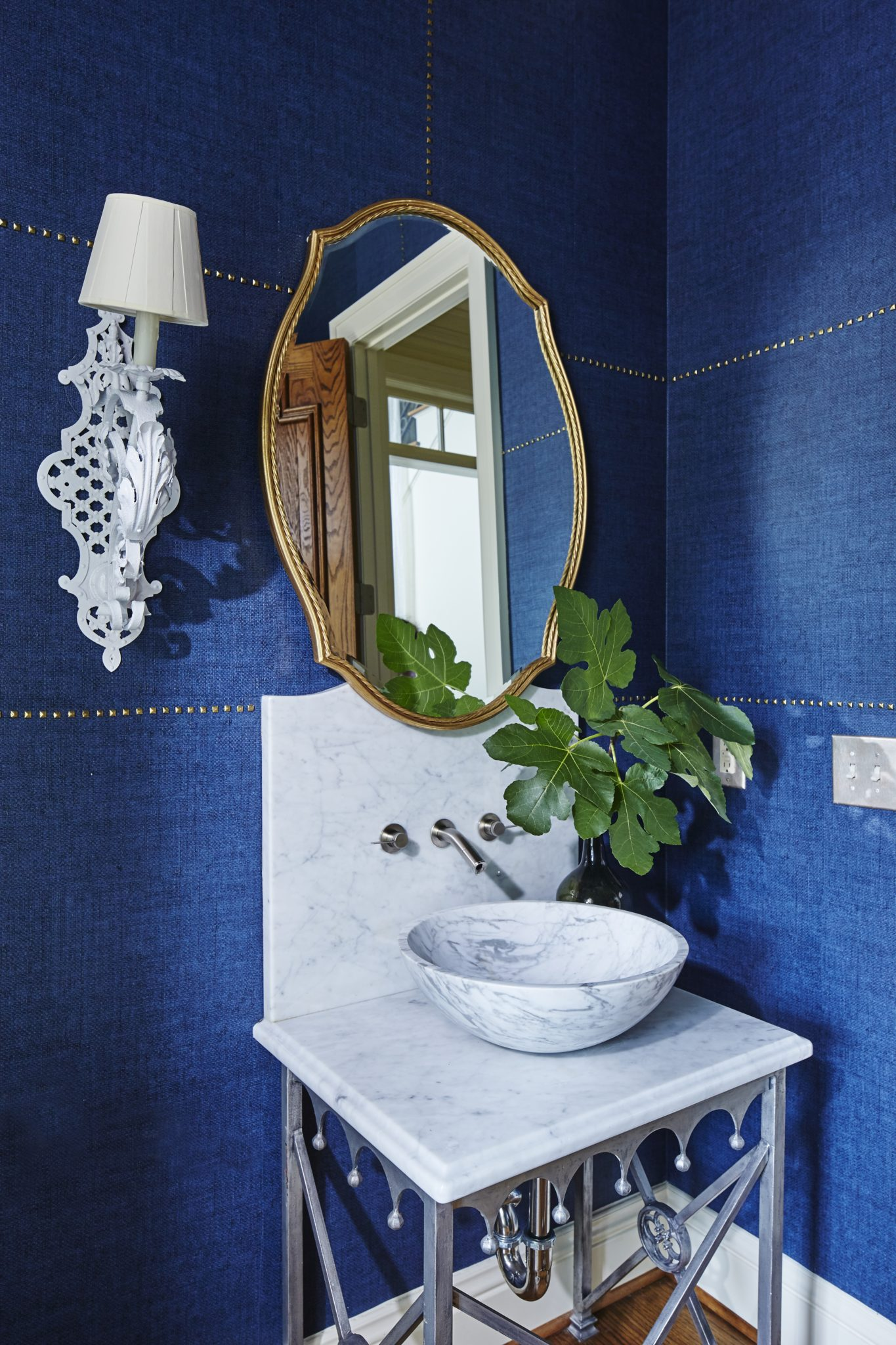 Powder bath with blue grasscloth walls and nailhead detail, marble sink basin. by Ashley Gilbreath Interior Design