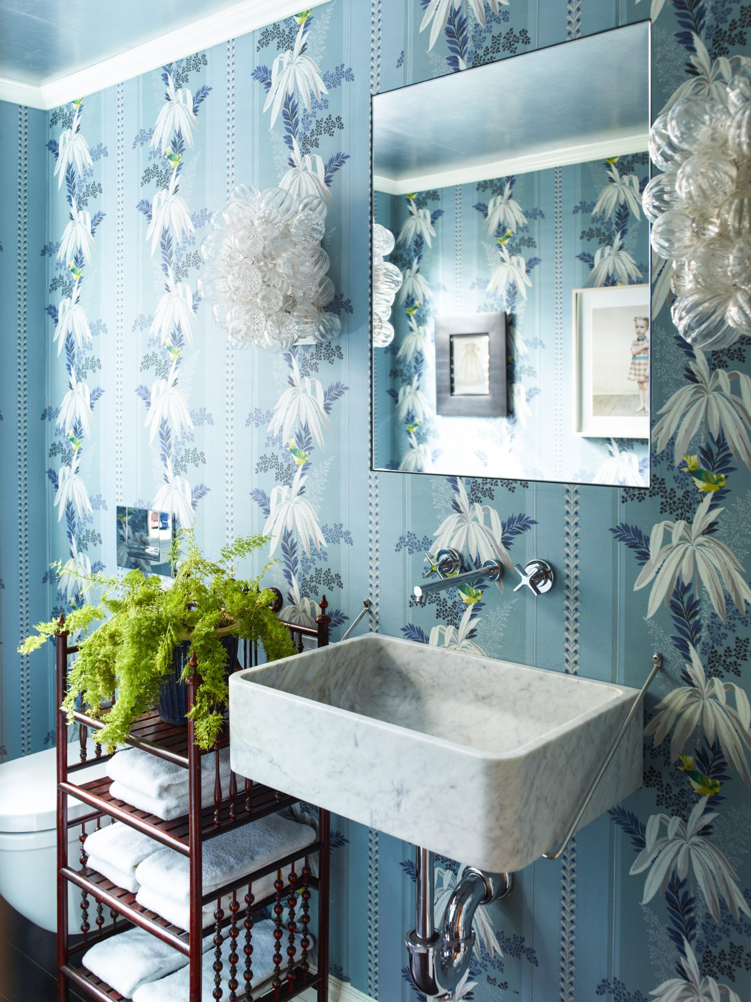 Powder room with blue, floral wallpaper by Katie Ridder Inc.