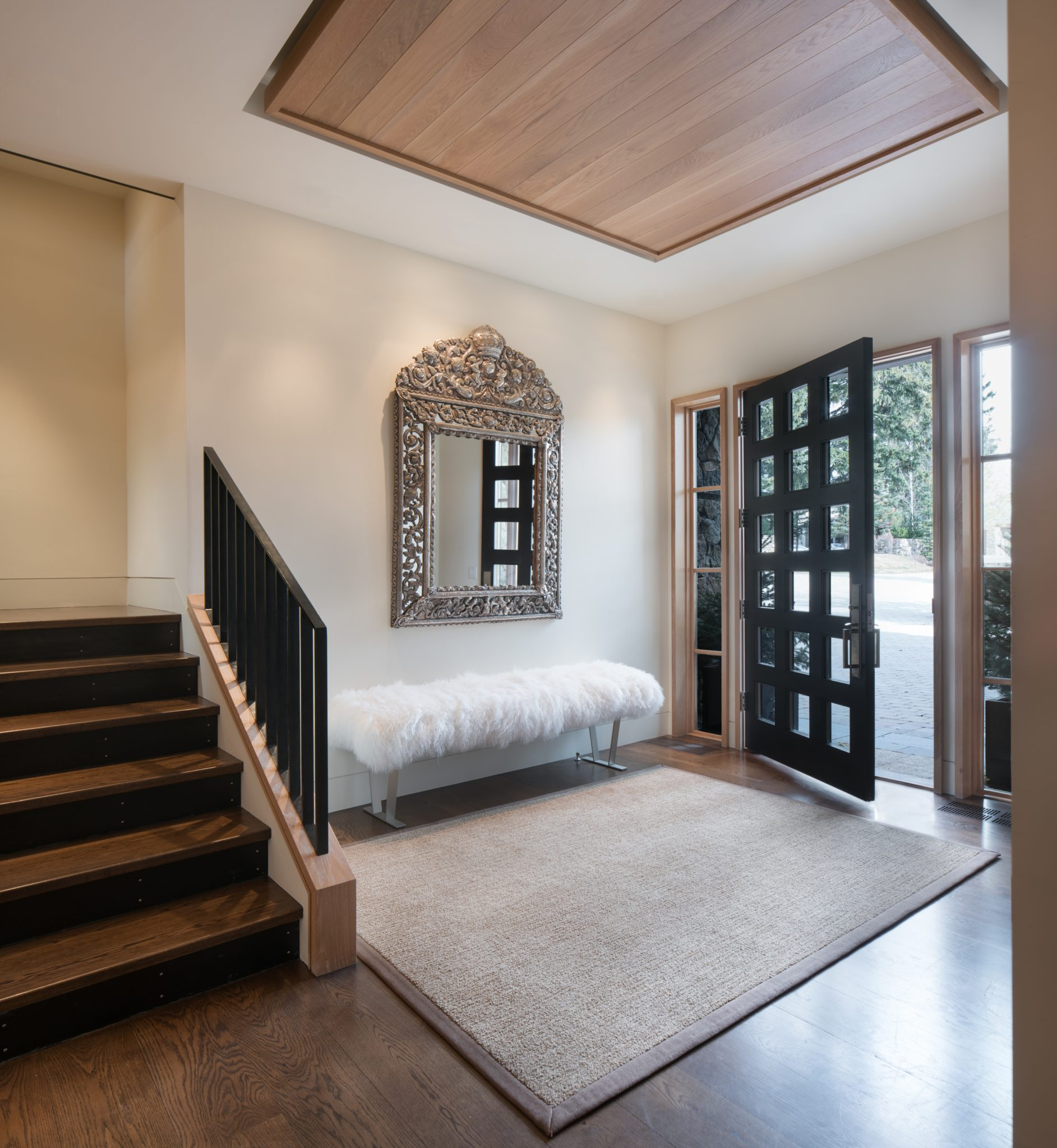 Contemporary mountain lodge entry with mongolian fur bench and Bolivian mirror by The Refined Group