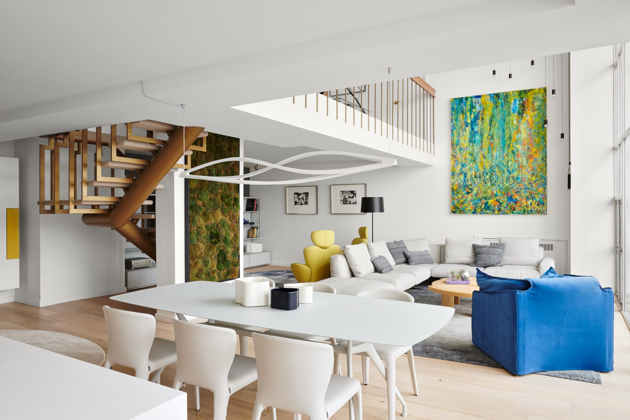 The moss artwork by abstract artist Nestor Toro ties in the blue of the armchair, as hanging pendant lights from Vibia, designed by Arik Levy, serves as an industrial accent.