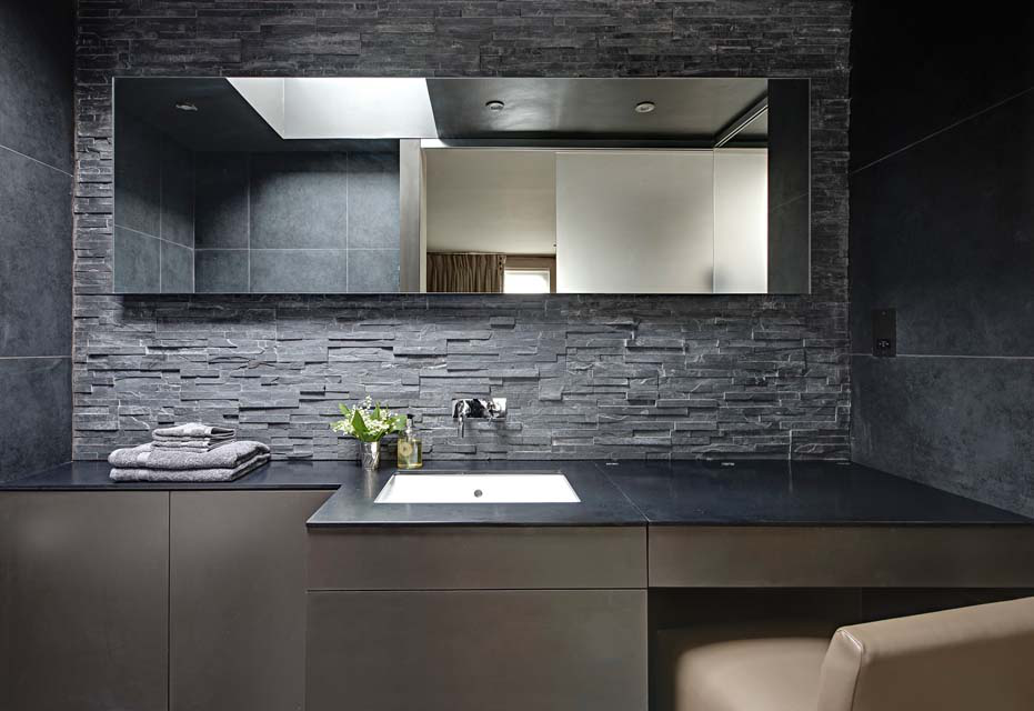 In the master bath, the custom cabinetry has a hidden makeup vanity and back-lit mirrors. The slate textured tiles and wall tiles are from Walton Ceramics.